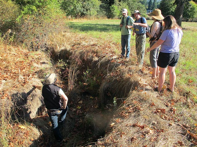 Wetlands INstitute Coordinator Neil Fletcher stands in a heavily-eroded stream bed while Tom Biebighauser speaks about restoration techniques.